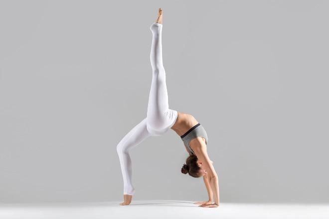 young-woman-one-legged-wheel-pose-grey-studio-background.jpg